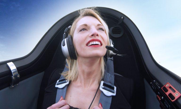 Tolle Aussichten - Frau schaut aus dem Flugzeugcockpit